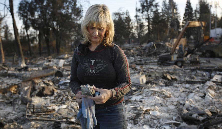 Debbie Wolfe stares at the broken figurine, she found in the burned ruins of her home Tuesday, Oct. 17, 2017, in Santa Rosa, Calif. A massive deadly wildfire swept through the area last week destroying thousands of housing and business. (AP Photo/Rich Pedroncelli)