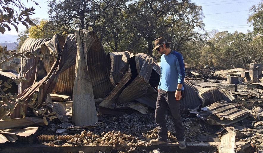 In this photo taken Oct. 15, 2017, Marcos Morales, co-founder of pot company Legion of Bloom, stands on the ruins of a state-of-the-art drying shed in Glen Ellen, Calif., where 1,600 pounds of ready-to-ship bud were destroyed in a fire. (AP Photo/Paul Elias)