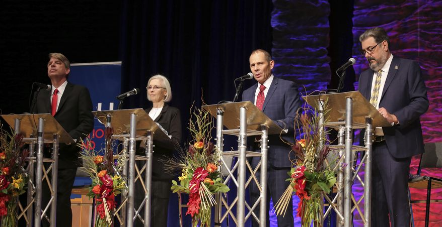 FILE - In this Friday, Oct. 13, 2017 file photo, United Utah Party's Jim Bennett, from left, Democrat Dr. Kathryn Allen, Republican John Curtis and Libertarian Joe Buchman attend Utah's 3rd Congressional District debate in a race to replace Jason Chaffetz in the U.S. House of Representatives in Sandy, Utah. The three candidates running to replace Chaffetz in the U.S. House of Representatives this November are meeting in their third debate Wednesday night, Oct. 18, 2017. (AP Photo/Rick Bowmer, File)