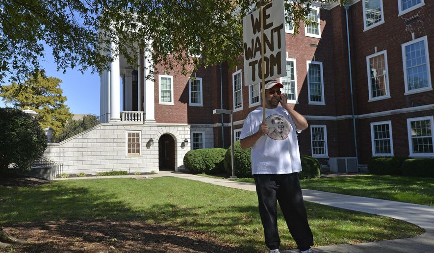 A supporter of University of Louisville Athletic Director Tom Jurich holds up a sign outside the University administration building, Wednesday, Oct.. 18, 2017, in Louisville, Ky. Jurich, suspended from his position as athletic director, is to meet with the board of trustees today. (AP Photo/Timothy D. Easley)