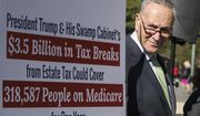 Senate Minority Leader Chuck Schumer, D-N.Y., stands beside a poster critical of the Republican tax and budget proposals during a news conference, at the Capitol in Washington, Wednesday, Oct. 18, 2017. (AP Photo/J. Scott Applewhite)