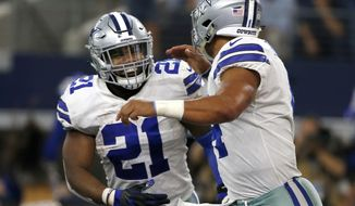In this Oct. 8, 2017, photo, Dallas Cowboys' Ezekiel Elliott (21) ad quarterback Dak Prescott (4) run off the field celebrating during an NFL football game against the Green Bay Packers in Arlington, Texas. Elliott on Tuesday, Oct. 17, was granted another legal reprieve in the running back's fight to avoid a six-game suspension over domestic violence allegations, clearing him to play Sunday at San Francisco. (AP Photo/Ron Jenkins)