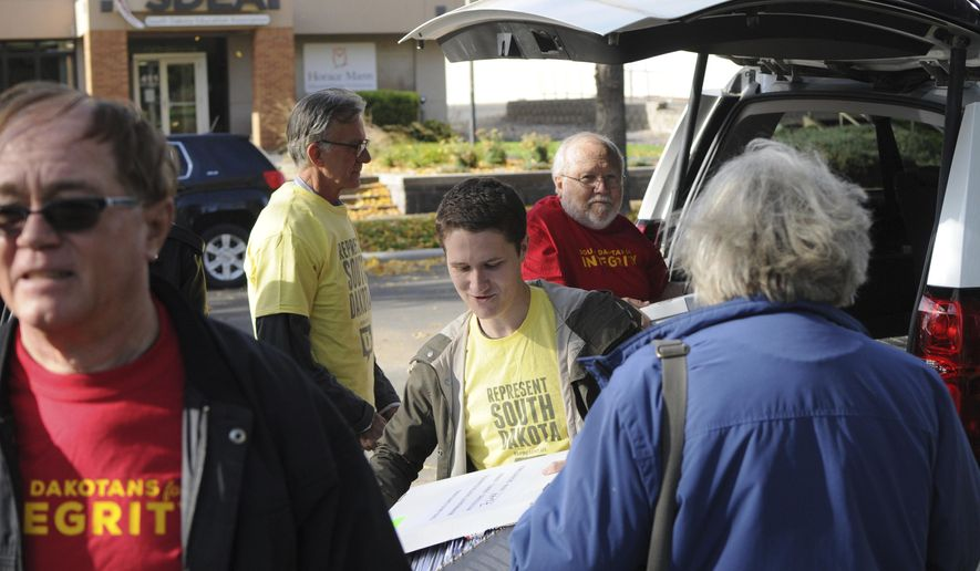 Represent South Dakota spokesman Doug Kronaizl, center, and other supporters of a proposed government ethics constitutional amendment unload boxes of petitions outside the state Capitol in Pierre, S.D., Wednesday, Oct. 18, 2017. The campaign says it turned in more than 50,000 signatures to the Secretary of State's office to put the measure on the 2018 ballot. (AP Photo/James Nord)
