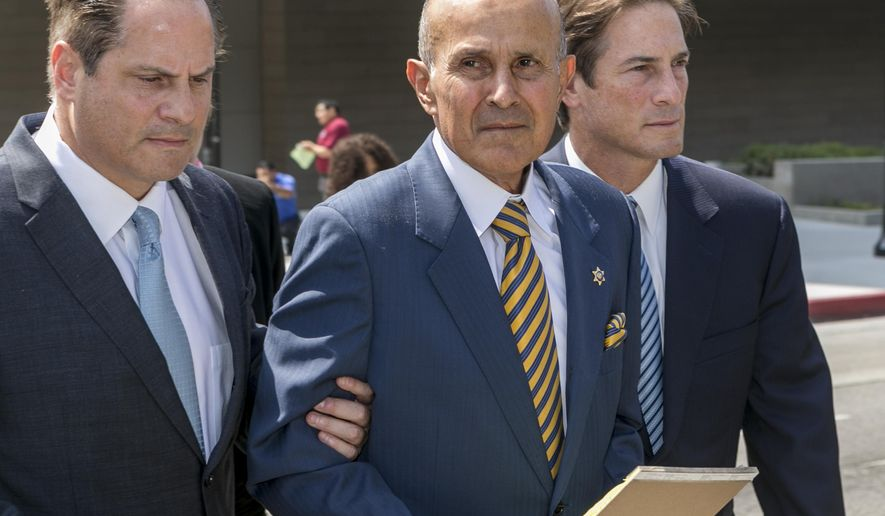 FILE--In this May 12, 2017, file photo, former Los Angeles County Sheriff Lee Baca, center, walks with attorneys, David Hochman, left, and Nathan Hochman, outside federal court in Los Angeles after he was sentenced to three years in prison for obstructing an FBI investigation into abuses at the jails he ran.  A federal appeals court says Baca should remain free while appealing his corruption conviction. (AP Photo/Damian Dovarganes, file)