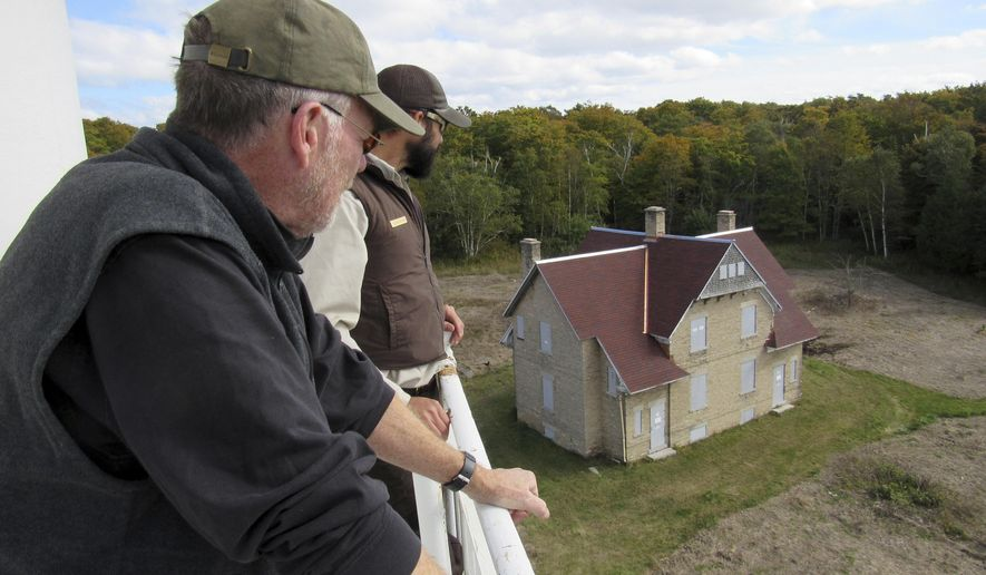 ADVANCED FOR MONDAY, OCT. 23, 2017 Dustan Hoffman, back, a ranger with the U.S. Fish & Wildlife Service, and John Lauber, an architectural historian and historic preservation planner from Minneapolis, look over the keepers quarters house as they stand on an outside observation deck of the rear range light on Plum Island in Door County Wednesday October 11, 2017. The Fish & Wildlife Service and the Friends of Plum & Pilot Islands are working to restore historic structures on the two islands located near Washington Island. (Barry Adams/Wisconsin State Journal via AP)