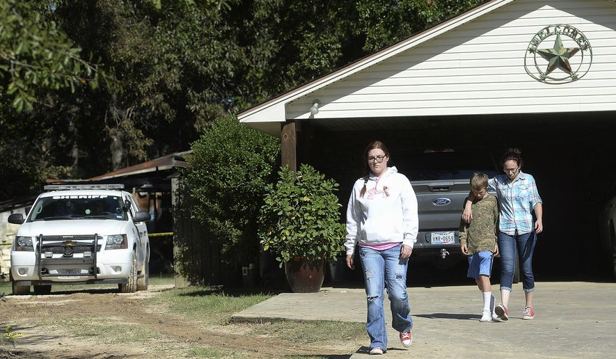 Family of those who were killed in a house fire make their way from a home in Silsbee, Texas, Wednesday, Oct. 18, 2017. A woman and her children were killed in a fire that quickly engulfed their Texas home, authorities said Wednesday. (Kim Brent/The Beaumont Enterprise via AP)