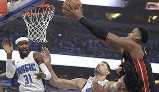 Miami Heat center Hassan Whiteside, right, puts up a shot over Orlando Magic guard Terrence Ross (31), center Nikola Vucevic, second from left, and guard Elfrid Payton during the first half of an NBA basketball game Wednesday, Oct. 18, 2017, in Orlando, Fla. (AP Photo/Phelan M. Ebenhack)