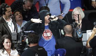 Eminem yells to the crowd before the start of an NBA basketball game between the Detroit Pistons and the Charlotte Hornets, Wednesday, Oct. 18,2017, in Detroit. (AP Photo/Carlos Osorio) **FILE**