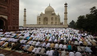 FILE- In this Aug. 20, 2012 file photo, Indian Muslims offer Eid al-Fitr prayer at Shahi Masjid at the famous Taj Mahal in Agra, India. India's famed monument of love, the white marble Taj Mahal, is finding itself at the heart of a political storm with some members of India's ruling Hindu right-wing party claiming that the mausoleum built by a Muslim emperor does not reflect Indian culture. (AP Photo/Rajesh Kumar Singh, File)