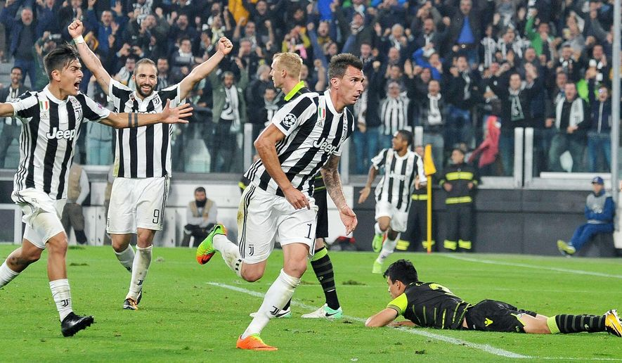 Juventus' Mario Mandzukic, center, celebrates after scoring during the Champions League group D soccer match between Juventus and Sporting Lisbon, at the Allianz stadium in Turin, Italy, Wednesday, Oct. 18, 2017. (Alessandro Di Marco/ANSA via AP)