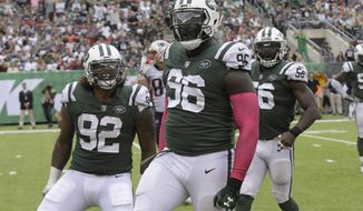 FILE - In this Oct. 15, 2017, file photo, New York Jets defensive end Muhammad Wilkerson (96), Leonard Williams (92) and Demario Davis (56) react during the second half of an NFL football game against the New England Patriots, in East Rutherford, N.J. The Jets and Dolphins face off on Sunday in Miami Gardens, Fla.  (AP Photo/Bill Kostroun, File)