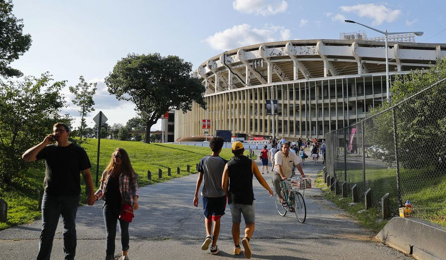 FILE - In this Aug. 5, 2017, file photo, people make their way to RFK Stadium in Washington before the start of an MLS soccer match between D.C. United and Toronto FC.  D.C. United will play their final game at RFK Stadium on Sunday. The United have already been eliminated from the playoffs, but they hope to say goodbye to the historic venue with a victory over the Red Bulls. (AP Photo/Pablo Martinez Monsivais, File) **FILE**