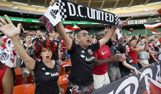 FILE - In this Aug. 1, 2015, file photo, D.C. United soccer fans, from left, Holly Renee Suarez, Johnny Mireles, and Drew Fletcher, cheer for their team during an MLS soccer match against Real Salt Lake in Washington. D.C. United will play their final game at RFK Stadium on Sunday. The United have already been eliminated from the playoffs, but they hope to say goodbye to the historic venue with a victory over the Red Bulls. (AP Photo/Manuel Balce Ceneta, File)