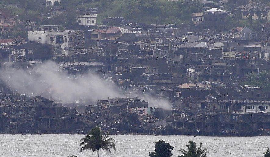 Smoke rises from the city as explosions continue to reverberate in Marawi, a day after President Rodrigo Duterte declared its liberation in the southern Philippines, Wednesday, Oct. 18, 2017. Sporadic explosions and gunfire continue Wednesday as Philippine soldiers fought to gain control of the last pocket of Marawi controlled by Islamic militants. (AP Photo/Bullit Marquez)