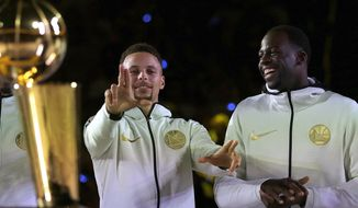 Golden State Warriors' Stephen Curry, left, gestures beside Draymond Green during an NBA championship ring ceremony prior to the basketball game against the Houston Rockets Tuesday, Oct. 17, 2017, in Oakland, Calif. (AP Photo/Ben Margot)