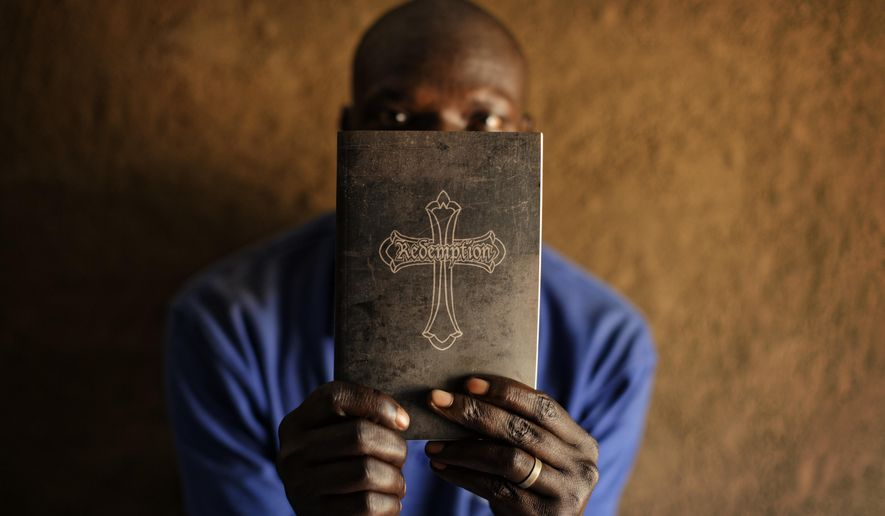 """In this photo taken Monday, June 5, 2017, a refugee pastor from the Yei area of South Sudan, who spoke on condition of anonymity for fear of retribution from South Sudanese intelligence officials, covers his face with his Bible inscribed with the word """"Redemption,"""" promising revenge, as he is photographed in his hut in Bidi Bidi refugee settlement in northern Uganda. When the region of Yei in South Sudan fell into ethnic cleansing in 2016, a handful of UN and US officials begged their leaders for help but the pleas fell on deaf ears, an AP investigation has found. (AP Photo/Ben Curtis)"""