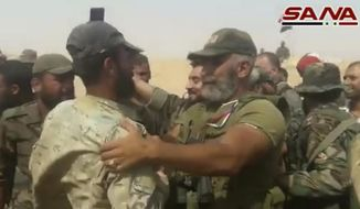 This frame grab from a video released on September 5, 2017 by the Syrian official news agency SANA, shows Syrian army senior commander Brig. Gen. Issam Zahreddine, right, who led the fight against Islamic Sate militants in the eastern city of Deir el-Zour congratulates a Syrian army soldier, at a front line, in Deir el-Zour, Syria. The Central Military Media said on Wednesday, Oct. 18, 2017, that Zahreddine was killed in Hawija Saqr, east of Deir el-Zour, in operations against IS militants. (SANA via AP)
