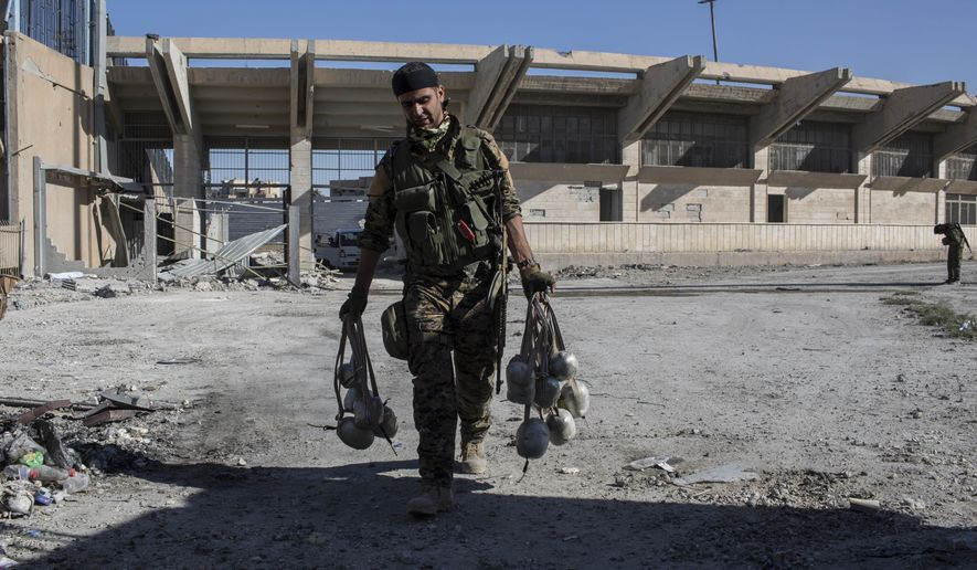 A member of U.S.-backed Syrian Democratic Forces (SDF) carries explosives at a stadium that that was the site of Islamic State fighters' last stand in the city of Raqqa, Syria, Wednesday, Oct. 18, 2017. SDF were removing land mines and clearing roads in the northern city a day after commanders said they had driven the Islamic State group from its de facto capital. (AP Photo/Asmaa Waguih)