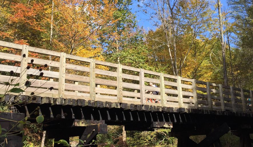 This Oct. 7, 2017 photo shows bikers crossing one of about 50 trestles and bridges that are part of the 34-mile Virginia Creeper Trail. The trail, stretching from Whitetop Station, Va., near the North Carolina border, and Abingdon, Va., is popular with bikers of varying ability levels. Outfitters will drop bikers at the top to enjoy the gentle downhill 17 miles to Damacus, and the more experienced bikers can continue the remaining 17 miles on flatter terrain into Abington. (AP Photo/Karen Testa)