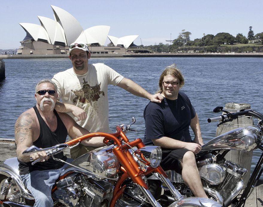 """FILE - In this Feb. 15, 2007, file photo, Paul Teutul Sr. left, and sons Paul Jr. center, and Mikey from the popular reality television show """"American Chopper"""" try out an Australian made chopper during a visit to Sydney, Australia. Discovery Channel announced on Oct. 18, 2017, it will revive the series in 2018. (AP Photo/Rob Griffith, File)"""