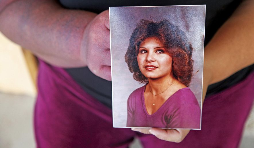 In this Friday, Sept. 29, 2017 photo, Sandra Padilla-Ramirez holds a photograph of her sister Peggy Sue Padilla at their family's home in Arroyo Seco in Espanola, N.M. Leonard Coriz, the boyfriend prosecutors say killed Padilla by running her over with his truck, claimed it was all an accident. Women are more likely to be killed by men in this state than nearly any other, according to an annual study published in Sept. 2017, by the Violence Policy Center.  (Gabriela Campos/Santa Fe New Mexican via AP)