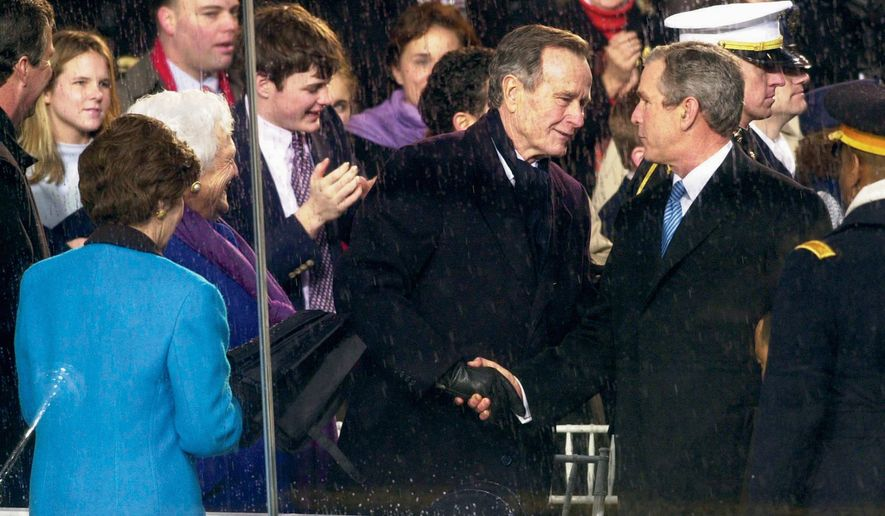President George W. Bush is congratulated by his father, former President George H.W. Bush, as he enters the reviewing stand in front of the White House after his inauguration on Jan. 20, 2001. (The Washington Times)