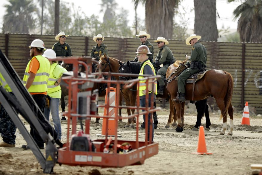 Border Patrol agents on horseback look on as crews work on border wall prototypes Thursday, Oct. 19, 2017, in San Diego. Companies are nearing an Oct. 26 deadline to finish building eight prototypes of President Donald Trump's proposed border wall with Mexico. (AP Photo/Gregory Bull)