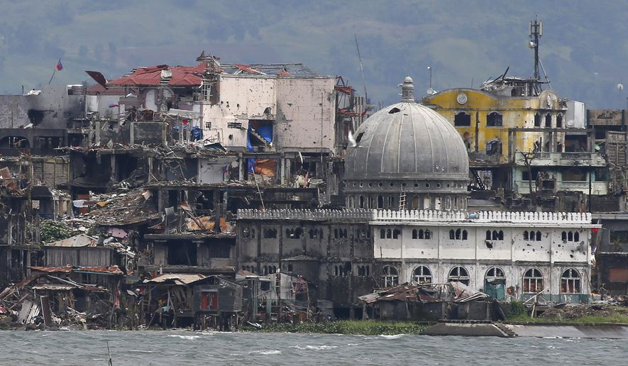 A mosque with its dome blasted out with holes is seen at the battle-scarred Marawi city in southern Philippines Thursday, Oct. 19, 2017. Two days after President Rodrigo Duterte declared the liberation of Marawi city, the military announced the killing of more suspected militants in the continuing military offensive. (AP Photo/Bullit Marquez)