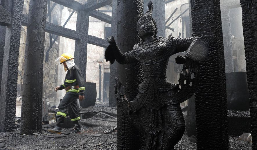 A firefighter walks at a burnt building following a fire at the Kandawgyi Palace Hotel Thursday, Oct. 19, 2017, in Yangon, Myanmar. A fire has nearly destroyed the luxury teakwood hotel popular with foreigners in Myanmar's biggest city of Yangon. (AP Photo/Thein Zaw)