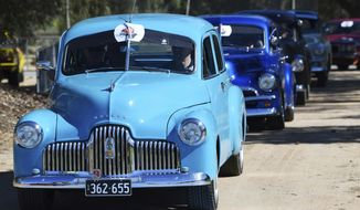 In this Oct. 15, 2017, historic Holden cars parade through the streets of Adelaide, Australia. The Australian auto manufacturing era ends after more than 90 years on Friday, Oct. 20, 2017 when General Motors Co.'s last Holden sedan rolls off the production line in the industrial city of Adelaide. The nation has already begun mourning the demise of a home-grown industry in an increasing crowded and changing global car market. (David Mariuz/AAP Image/ via AP)
