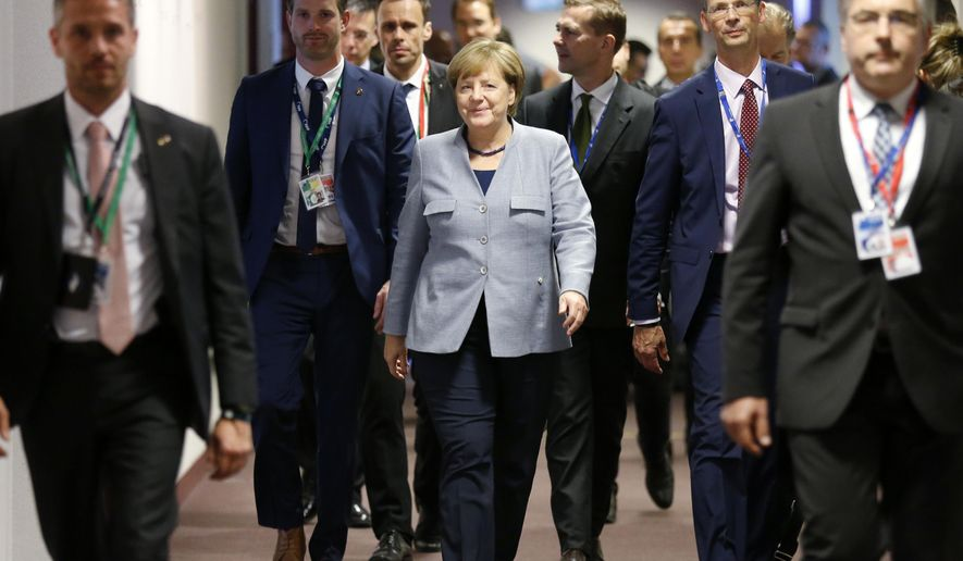 German Chancellor Angela Merkel, center, walks to a meeting on the sidelines of an EU summit in Brussels on Thursday, Oct. 19, 2017. British Prime Minister Theresa May headed to a European Union summit Thursday with a pledge to treat EU residents well once Britain leaves the bloc. (Francois Lenoir, Pool Photo via AP)