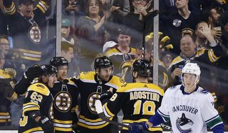 Boston Bruins' Patrice Bergeron (37) celebrates with teammates from left, Brad Marchand; David Pastrnak, of the Czech Republic; and Kenny Agostino as Vancouver Canucks' Troy Stecher (51) skates away during the third period of an NHL hockey game in Boston, Thursday, Oct. 19, 2017. The Bruins won 6-3. (AP Photo/Michael Dwyer)