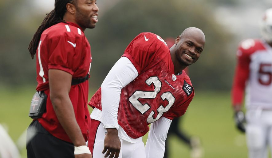 Running back Adrian Peterson, right, smiles alongside wide receiver Larry Fitzgerald of the Arizona Cardinals laugh during an NFL training session at the London Irish rugby team training ground in the Sunbury-on-Thames, a suburb of south west London, Thursday, Oct. 19, 2017. The Arizona Cardinals are preparing for an NFL regular season game against the Los Angeles Rams in London on Sunday. (AP Photo/Kirsty Wigglesworth)