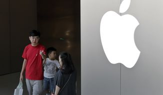 FILE - In this July 30, 2017, file photo, a Chinese family walks out of an Apple store in Beijing. Hundreds of workers protested Wednesday night, Oct. 18, 2017, over bonuses promised through labor brokers who recruited them to work at Jabil Inc.'s Green Point factory, an Apple supplier, in Wuxi city in southern China, according to witnesses. (AP Photo/Andy Wong, File)