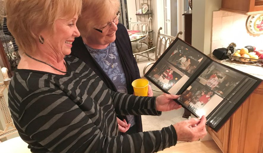 In this Sept. 2017 photo Judy Schonhoff, left, holds a photo album while reminiscing with  Jayne Lammers in Judy's kitchen in Quincy, Ill. Schonhoff and Lammers are part of a group of seven couples that have been meeting monthly for the last 35 years. Jim and Judy Schonhoff attended a Marriage Encounter 35 years ago, two weeks after tying the knot. They didn't expect to develop friendships with the six sets of strangers they were paired with at the encounter. No one there expected to walk away with such a large group of lifelong friends. (Matt Dutton/The Quincy Herald-Whig via AP)