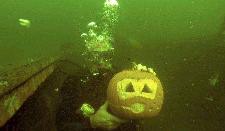 In this Sunday, Oct 15, 2017, photo, Scuba Diver, Matt Williamson, of Etlderton, shows off his Jack-O'-Lantern with a Scuba theme during his under water pumpkin carving experience at Crusy's Quarry, in Slippery Rock, Pa. Scott's Scuba owner Scott Camerlo said the challenges of carving a pumpkin about 20 feet underwater are their buoyancy and lessened gravity. (Louis B. Ruediger /Pittsburgh Tribune-Review via AP)