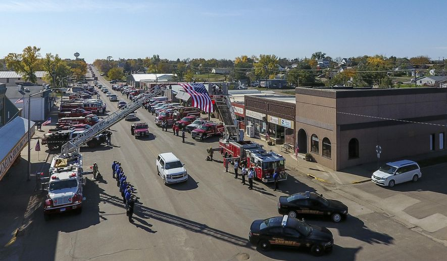 "The funeral procession for Donald ""Donny"" Manger is led by a pair of Lyman County Sheriff's patrol cars followed by his immediate family in the white SUV and directly followed by a Presho Fire Department vehicle carrying Manger down Main Avenue in Presho, S.D., Thursday, Oct. 19, 2017. Manger died over the weekend after suffering a medical condition while fighting a fire. (Matt Gade/The Daily Republic via AP)"