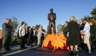 A statue of Philadelphia Flyers founder Ed Snider is unveiled at a ceremony attended by his family, friends and members of the Flyers NHL hockey organization outside the Wells Fargo Center, Thursday, Oct. 19, 2017, in Philadelphia. (Yong Kim/The Philadelphia Inquirer via AP)