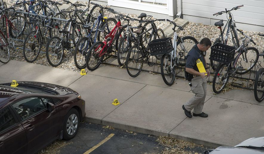 An investigator marks evidence while working the scene of an early morning homicide Thursday,, Oct. 19, 2017, in Fort Collins, Colo. The fatal shooting took place outside a housing complex about a mile west of Colorado State University. (Timothy Hurst /The Coloradoan via AP)