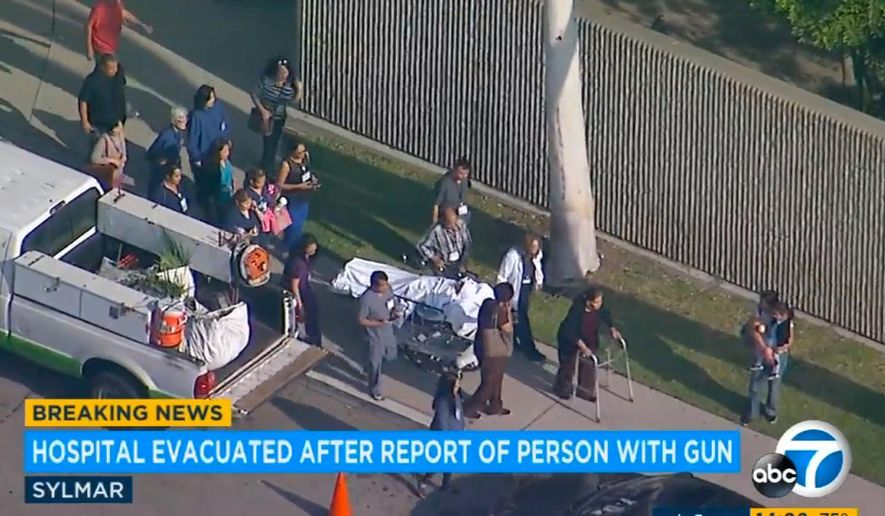 This image made from a video provided by KABC-TV shows employees and patients being evacuated from the Olive View-UCLA Medical Center in the Sylmar section of Los Angeles on Thursday, Oct. 19, 2017. Employees, visitors and patients in wheelchairs and on gurneys streamed out of the Los Angeles hospital as it was partially evacuated Thursday following a report of a possible person with a gun, sheriff's officials said. (KABC-TV via AP)