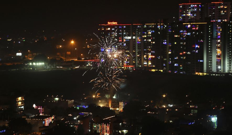 Residential buildings are decorated with colorful lights, as a firecracker lights up, during Diwali festival in New Delhi, India, Thursday, Oct. 19, 2017. Worried especially by the impact on the health of children, the Supreme Court this year banned the sale of firecrackers, that is usually in huge demand across the country as the evening sky is lit up by the festivities, in the Indian capital and neighboring areas to prevent a toxic haze after the Diwali nights that has residents hiding indoors. (AP Photo/Altaf Qadri)