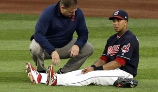FILE - In this Aug. 8, 2017, file photo, Cleveland Indians' Michael Brantley, right, is looked at by a trainer in the fifth inning of a baseball game against the Colorado Rockies, in Cleveland. Brantley had surgery to repair a right ankle injury that limited him in the playoffs. Brantley had ligaments stabilized in his ankle, which he injured while playing left field on Aug. 8.  (AP Photo/Tony Dejak, File)