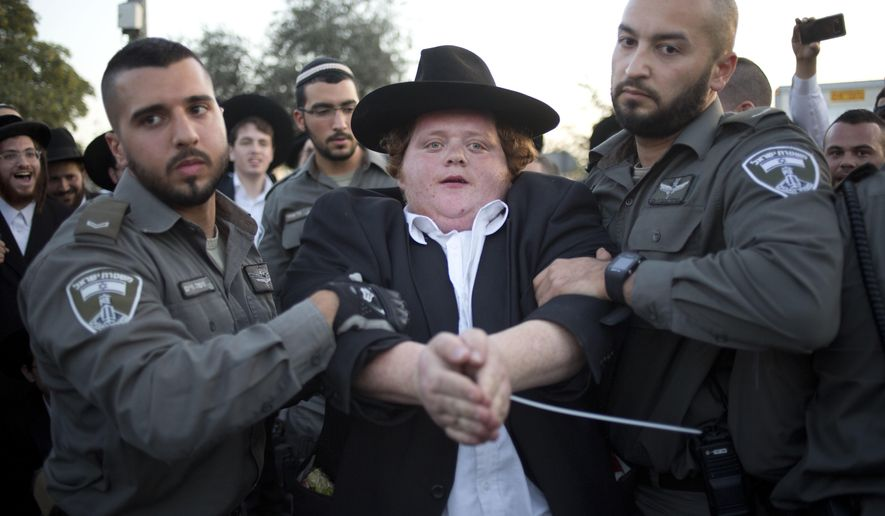 Israeli Police officers arrest an ultra-Orthodox Jew as they block a main road during a protest against Israeli army conscription, in Jerusalem, Thursday, Oct. 19, 2017. Israeli police say they have arrested 40 people in protests by a fringe group within Israel's ultra-Orthodox Jewish community. (AP Photo/Ariel Schalit)