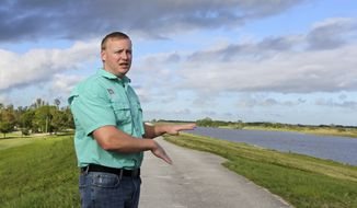 Almur Whiting of the Army Corps of Engineers talks to reporters Thursday, Oct. 19, 2017, in Clewiston, Fla. Whiting said there has been some seepage through the Herbert Hoover Dike but it is not significant. Federal officials are conducting daily inspections of the dike that surrounds Lake Okeechobee because of its near-record water levels but say it is not in danger of failing. (AP Photo/Alan Diaz)