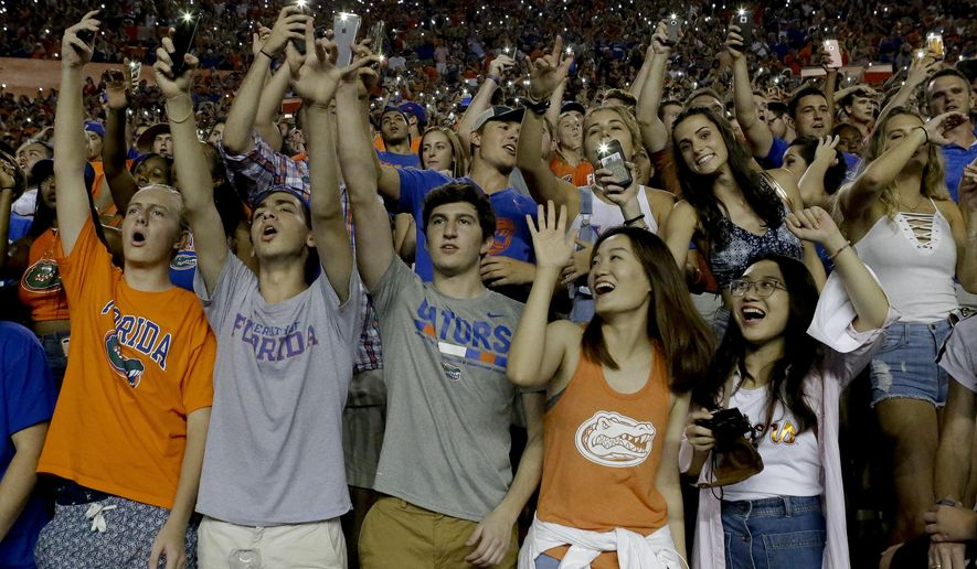 "In this Oct. 14, 2017, photo, Florida fans wave cell phone lights and sing the Tom Petty song ""I Won't Back Down"" at the beginning of the fourth quarter of the team's NCAA college football game against Texas A&M in Gainesville, Fla. This is a new tradition to honor Gainesville native Tom Petty, who died earlier this month. (AP Photo/John Raoux)"