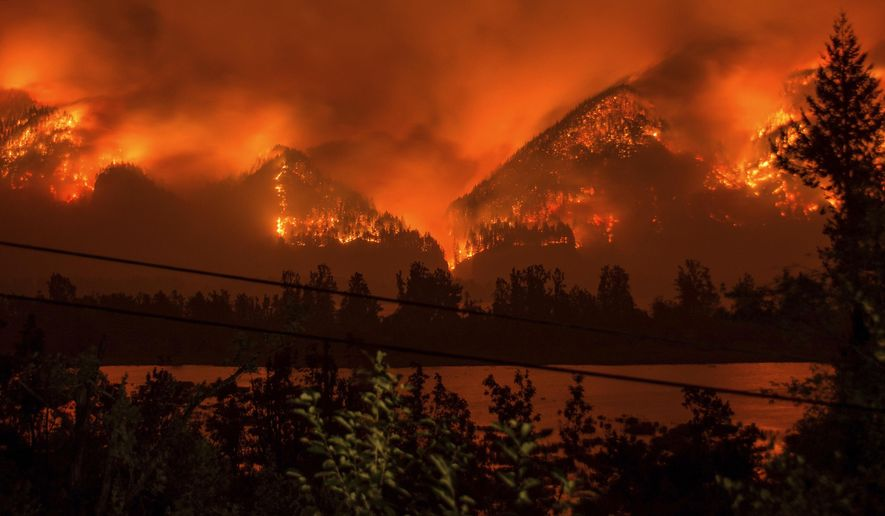 FILE - This Sept. 4, 2017 file photo provided by KATU-TV shows a wildfire seen from Stevenson, Wash., across the Columbia River, burning in the Columbia River Gorge above Cascade Locks, Ore. Charges have been brought against a 15-year-old boy who allegedly used fireworks to start the blaze. The Hood River County District Attorney said in a statement Thursday, Oct. 19 that the charges in juvenile court include reckless burning, depositing burning materials on forest lands and recklessly endangering other persons. (Tristan Fortsch/KATU-TV via AP, File)