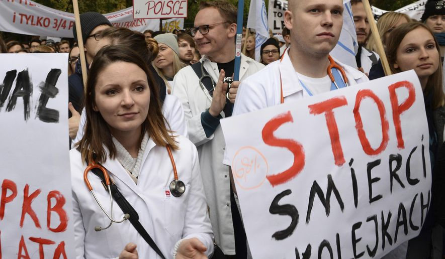 Young doctors rally in front of the prime minister's office to demand increases of their low earnings and more spending on the chronically strapped and inefficient health care, in Warsaw, Poland, Saturday, Oct. 14, 2017. The placard right reads: Stop dying in queues. (AP Photo/Alik Keplicz)