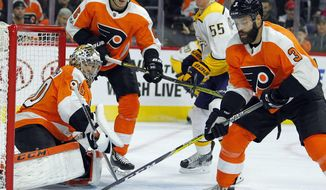 Philadelphia Flyers' Radko Gudas, right, clears the loose puck from the crease as goalie Michal Neuvirth and defenseman Travis Sanheim and Nashville Predators' Cody McLeod watch during the first period of an NHL hockey game Thursday, Oct. 19, 2017, in Philadelphia. (AP Photo/Tom Mihalek)