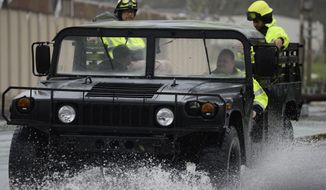 FILE - In this Sept. 20, 2017 file photo, rescue personnel drive on a road flooded by the heavy rains brought on by Hurricane Maria, in Humacao, Puerto Rico. The storm swept across the island causing at least 48 deaths, according to the official tally. It caused widespread flooding and knocked out the entire power grid for the island of 3.4 million people. (AP Photo/Carlos Giusti, File)