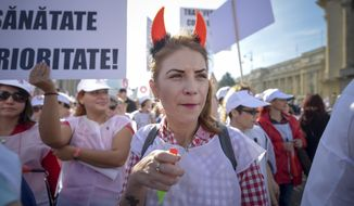 A Romanian public health worker wearing devil horns reacts during a protest in Bucharest, Romania, Thursday, Oct. 19, 2017. Some 7,000 Romanian public sector health workers are demonstrating in the capital, demanding the government scrape its plan to make workers pay more social security taxes. (AP Photo/Andreea Alexandru)